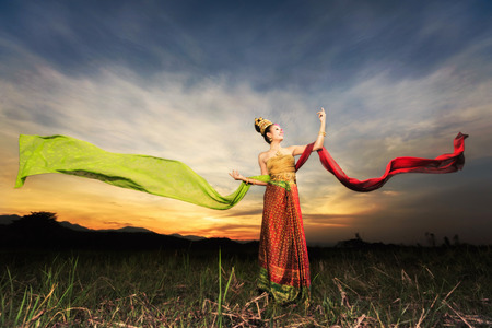 Thai dancing girl with northern style dress in rice field in front off background of sunset photo