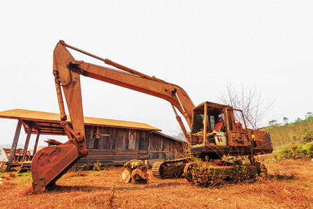 Old excavator standing with sunset background photo