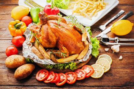 Whole roasted chicken with vegetables on wood table Stock Photo