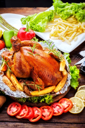 Whole roasted chicken on table background Stock Photo