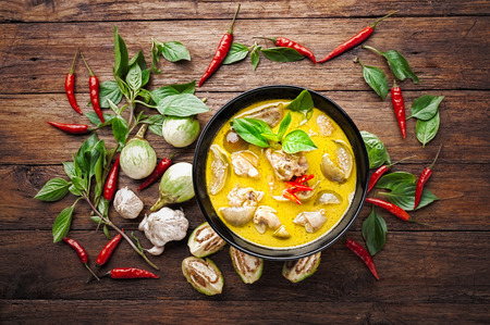 Thai food green curry chicken on wooden background. top view