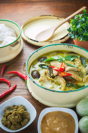 Thai food green curry chicken on wooden background.