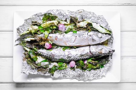 Steamed Saba fish with soy sauce and vegetable in foil on white plate and white wooden table Stock Photo