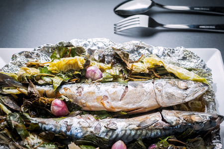 Steamed Saba fish with soy sauce and vegetable in foil on white plate Stock Photo