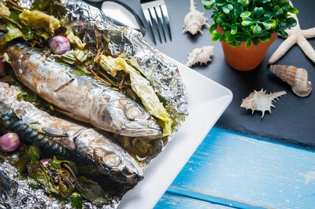 Steamed Saba fish with soy sauce and vegetable in foil on white plate and blue wooden table Stock Photo