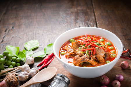 Red curry with pork and coconut milk, delicious Thai food on wooden table.