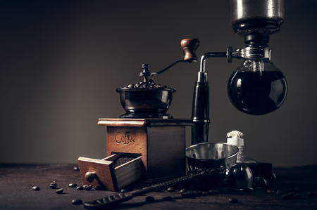 Japanese siphon coffee maker and coffee grinder on old kitchen table background, It is very fragrant and aroma because filled with fresh coffee beans. Stock Photo