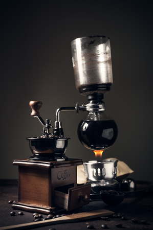 Japanese siphon coffee maker and coffee grinder on old kitchen table