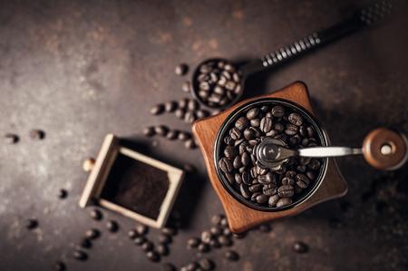 Schöne Kaffeemühle und Kaffeebohne auf altem Küchentischhintergrund.