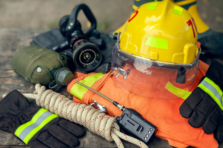 Outfit of Firefighter placed on wooden table background, Fire equipment concept.