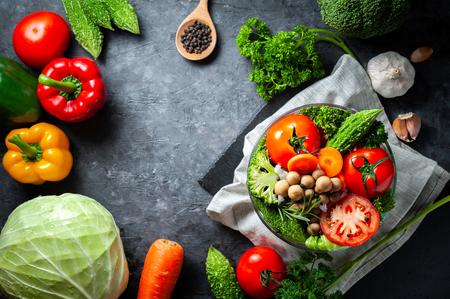 Vari alimenti biologici di verdure fresche per un sano su fondo rustico scuro con spazio di copia per il testo.