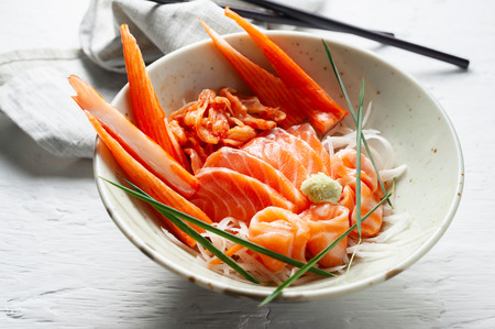 Salmon sashimi and imitation crab stick in Japanese style with kimchi, wasabi.