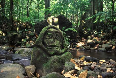 polynesia: Old stone carving rests in the tropical rainforest of Moorea, French Polynesia Stock Photo