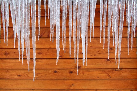 Icicles hang from a wood cabin in on a chilly winter day in northern America