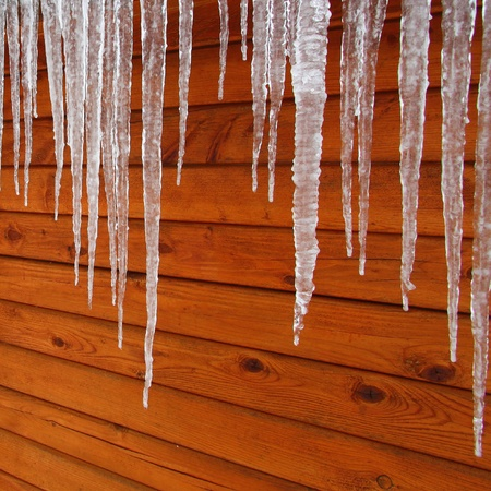Icicles hang from a wood cabin in on a chilly winter day in northern Illinois Stock Photo - 8779154