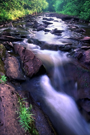 gleams: Sunlight gleams off the smooth waters of a stream nestled in the Porcupine Mountains Wilderness State Park of Michigan Stock Photo
