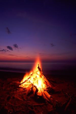 Blazing campfire at sunset along the beautiful beach of Lake Superior in northern Michigan Stok Fotoğraf