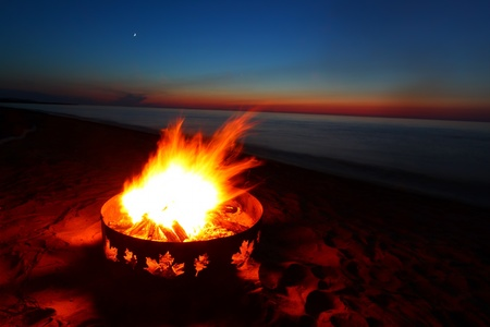 Campfire and beautiful sunset along the beautiful beach of Lake Superior in northern Michigan Stock Photo