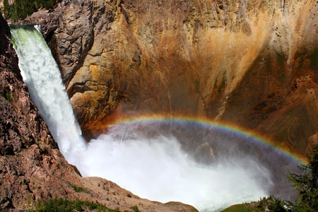 Sunlight creates a rainbow in mists of the Lower Falls of the Yellowstone River in Wyoming photo