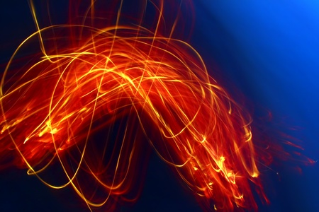 Vivid swirls of flame light up a dark blue evening sky Stock Photo