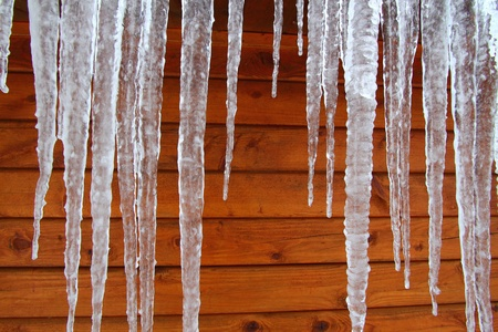 Icicles hang from a wood cabin in on a chilly winter day in northern America. Stock Photo