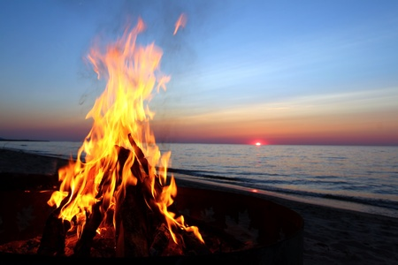 Blazing campfire at sunset along the beautiful beach of Lake Superior in northern Michigan photo