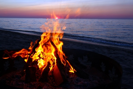Blazing campfire at sunset along the beautiful beach of Lake Superior in northern Michigan Stock Photo