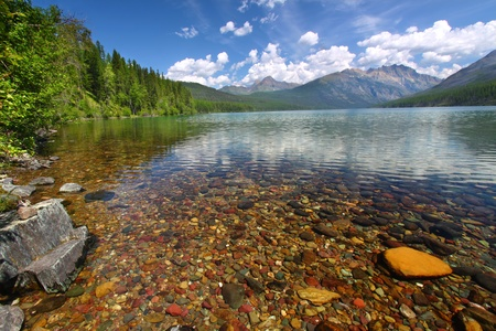 Brightly colored rocks seen through the crystal clear waters of Kintla Lake in Glacier National Park - USA