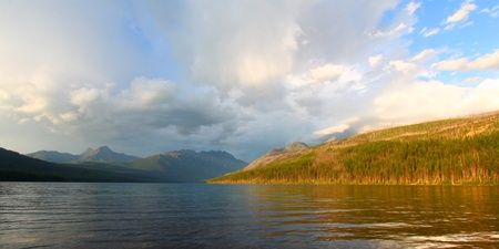 Sunlight illuminates the shoreline of Kintla Lake against a stormy sky in Glacier National Park - USA photo