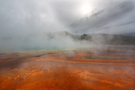 Steam rises from the surface of Grand Prismatic Spring on a cool fall day - Yellowstone National Park photo