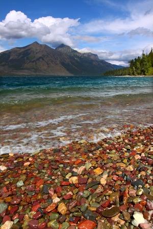 Small waves trickle through bright glacial rocks of Lake McDonald in Glacier National Park