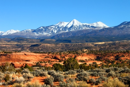 capped: Snowcapped Mount Tukuhnikivatz of the Monti-La Sal National Forest rises above the red rock landscape in Utah