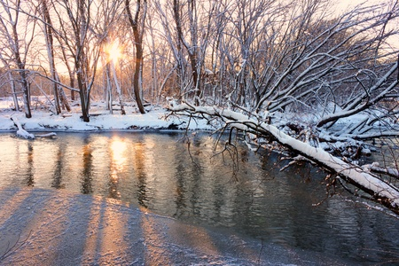 winter road: Light of sunset sparkles off the Kishwaukee River in northern Illinois