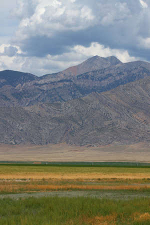 Mountains rise tall beyond a flat agricultural valley of Idaho photo