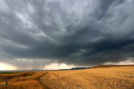 Dark storm clouds thunder across the plains of rural Montana on a fall day