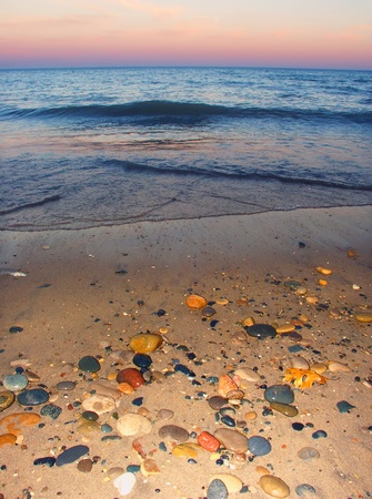 Smooth stones dot the sand at sunset over Lake Michigan at Illinois Beach State Park photo