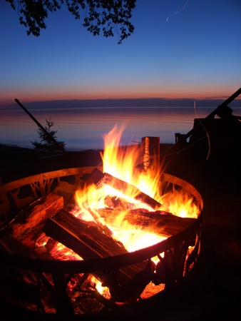 upper peninsula: Blazing campfire at sunset along the beautiful beach of Lake Superior in northern Michigan Stock Photo