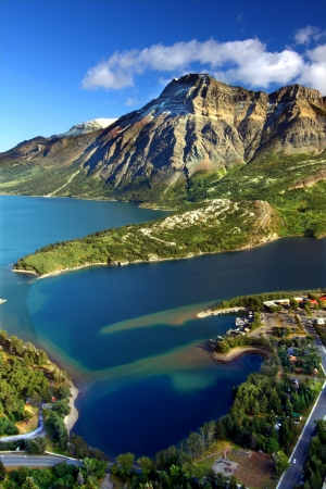 Sweeping view over blue waters and rugged mountain peaks of Waterton Lakes National Park in Canada