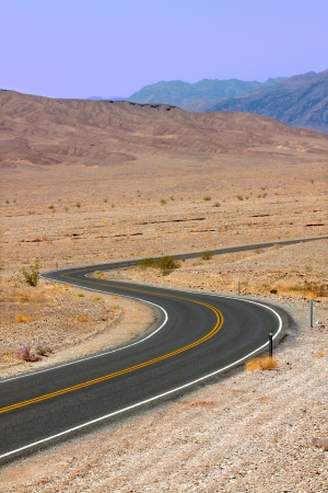 Long winding road through the hot deserts of Death Valley in California photo