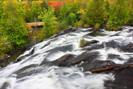 Autumn foliage surrounds the cascading waters of Bond Falls in northern Michigan photo