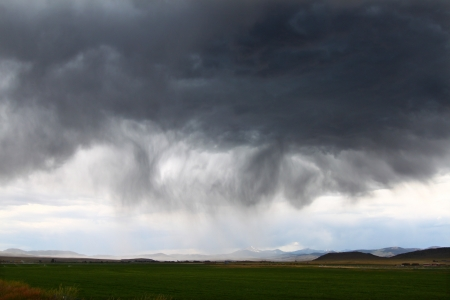precipitation: Dark clouds and precipitation from a thunderstorm in rural Idaho Stock Photo