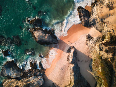 A top view of a beach with rock formations in Porto Covo, Portugal