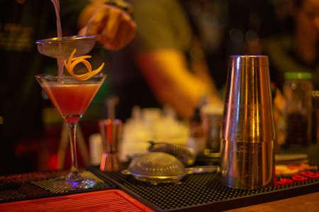 A closeup shot of a bartender making a red cocktail on a bar counter 免版税图像