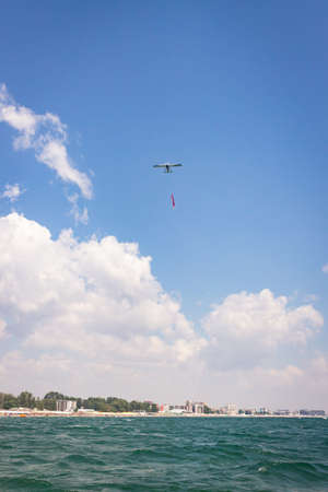 A vertical shot of a monoplane above the Rimini beach in Italy