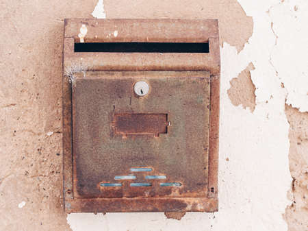 An old rusty metal mailbox hanging on a wall at daytime