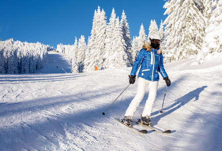 A skier riding down the hill in the mountain resort with beautiful winter forest scenery in the background