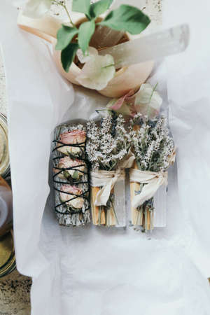 An overhead shot of beautifully arrange smudge sticks on white wrapping paper