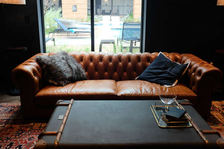 A modern interior of a lounge with brown leather couch and modern decors