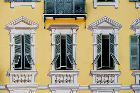 The windows of a building with a yellow facade in Place Garibaldi in Nice, France