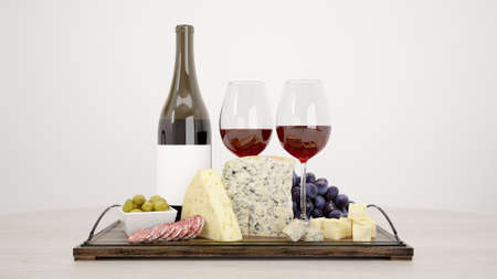 A closeup of a board with cheese, grapes and a bottle of wine with two glasses on it on the table 免版税图像